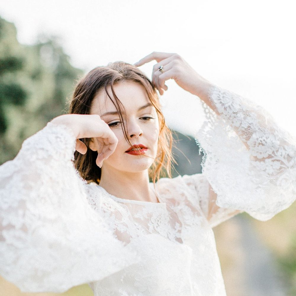 Red lips-warm brown eyeshadow-messy low bun-outdoor wedding-rustic-natural bouquet