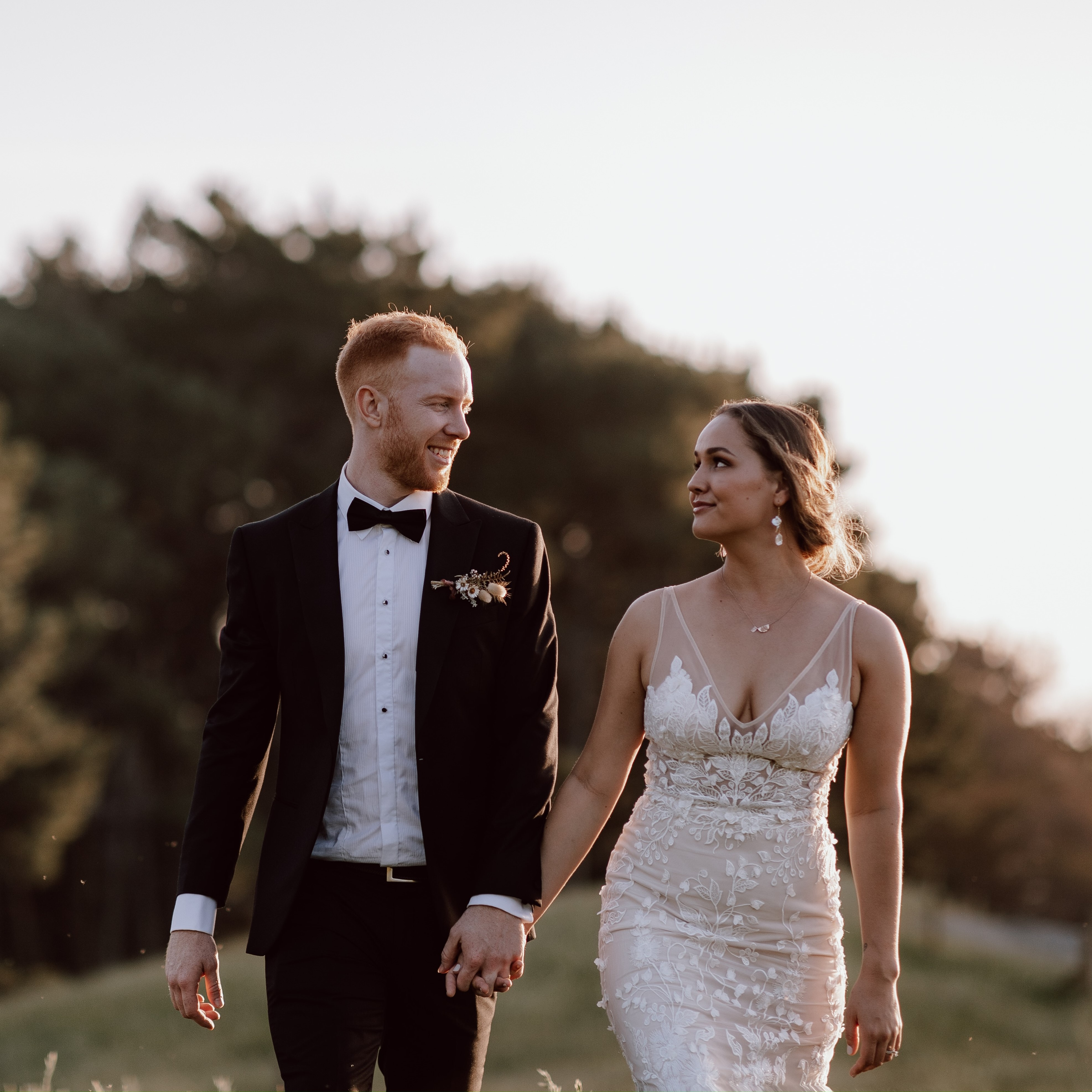 A bride and groom standing in a meadow holding hands in the sunset and the bride has her hair styled in a low messy bun