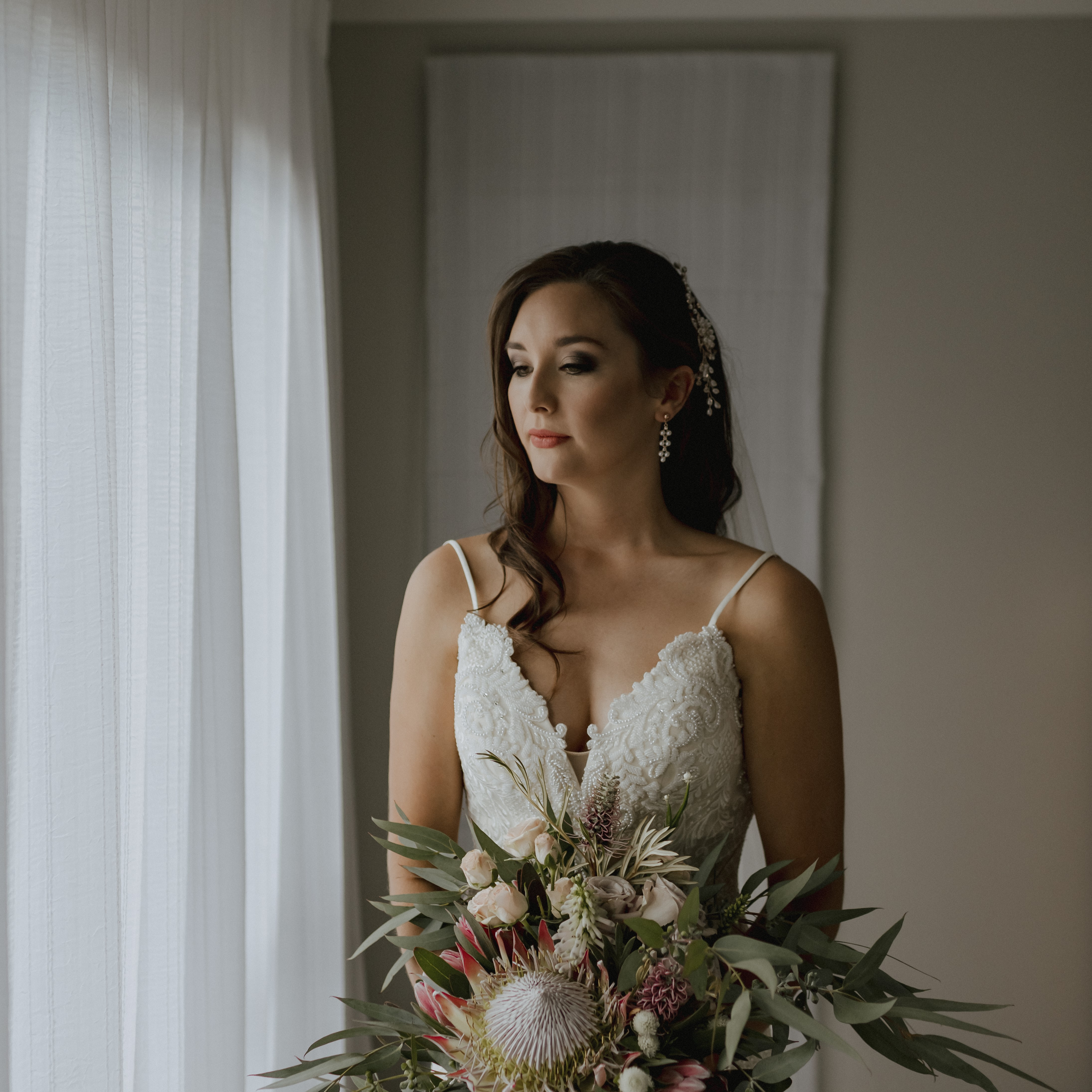 Bride looking down-dark smokey eyes, nude lips and hollywood waves with hair clip-holding her large bouquet