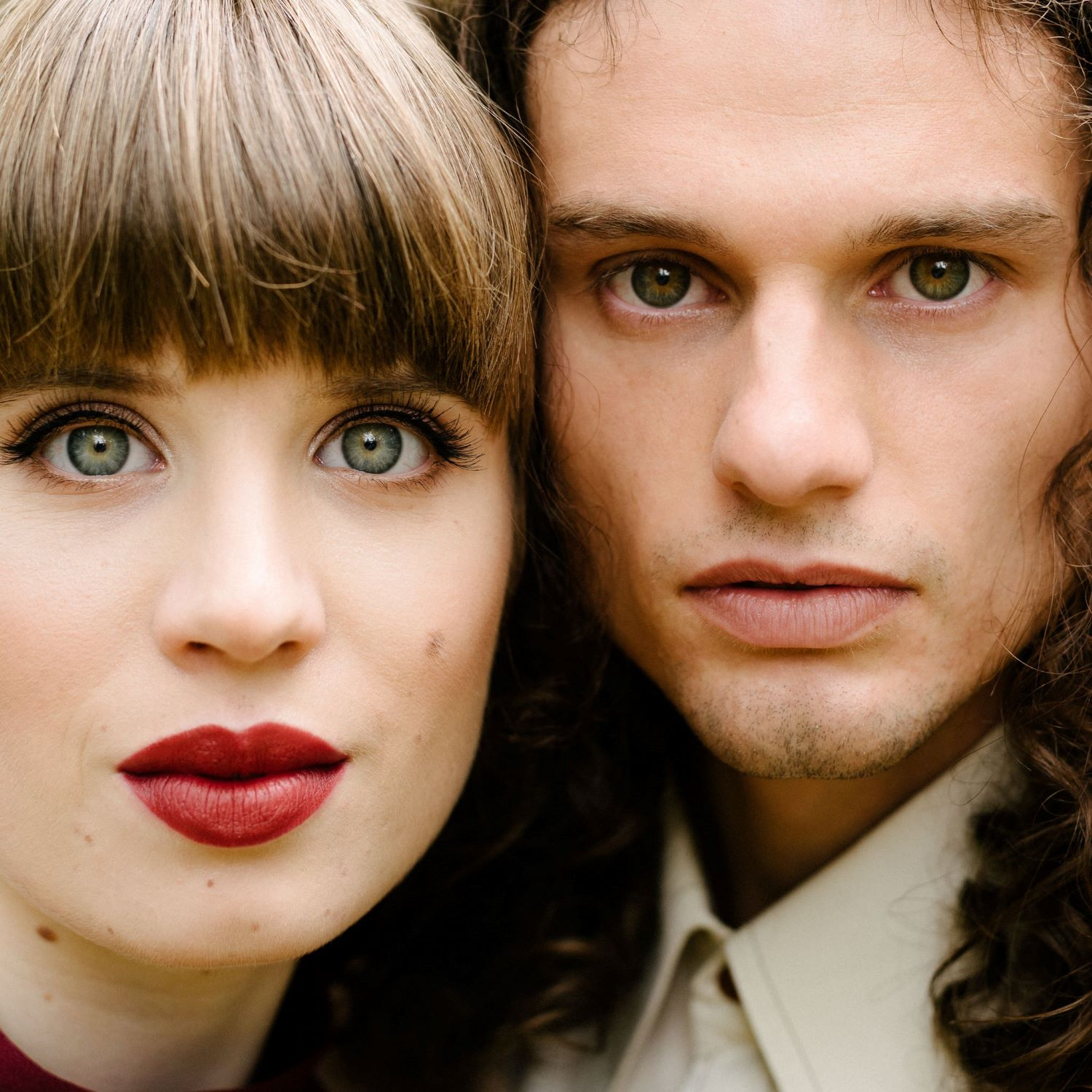 Close up of couple-girls wearing makeup of bold red lips and winged eyeliner