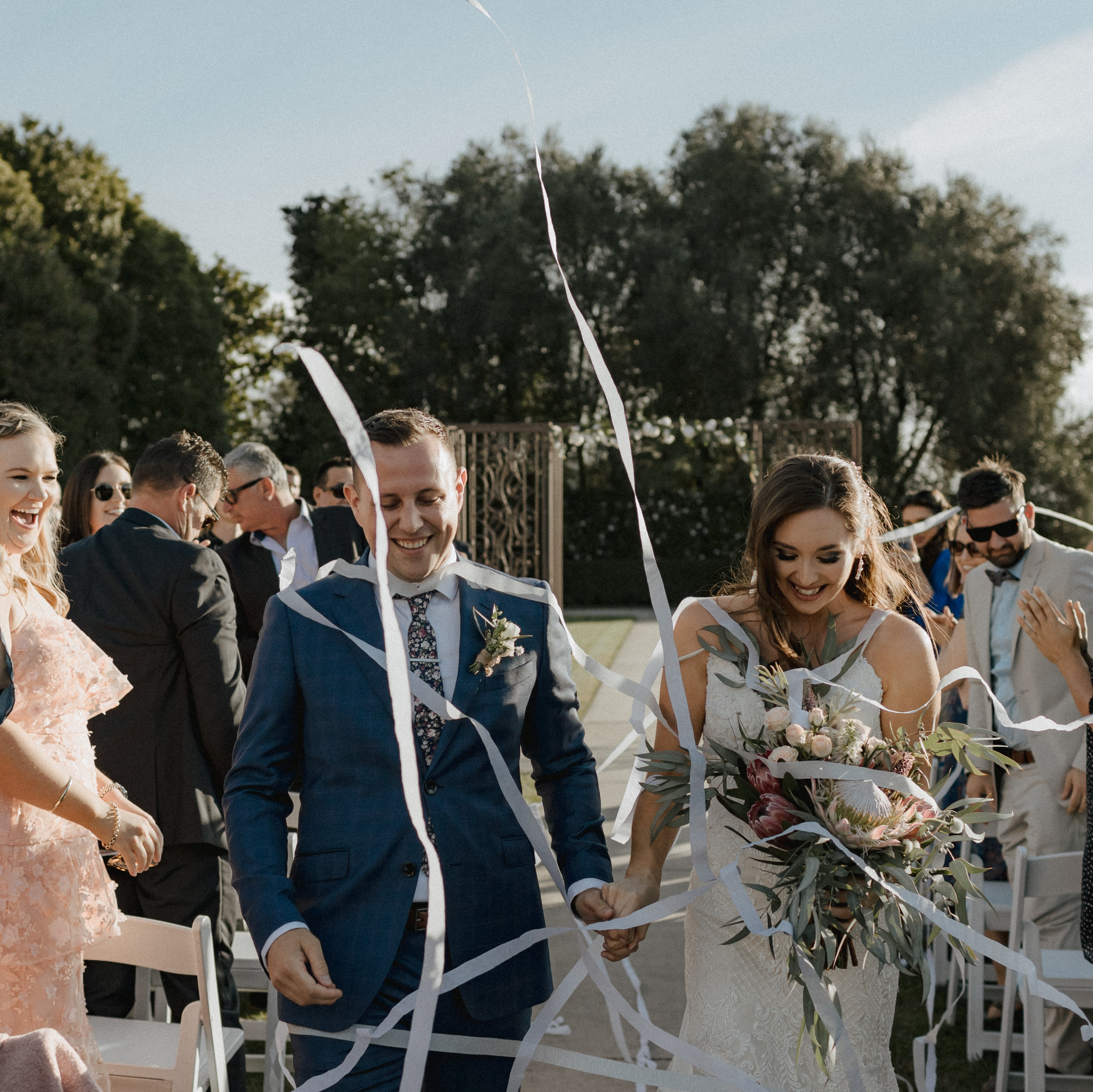 bride and groom walking down isle holding hands-confetti being thrown by guests-laughter