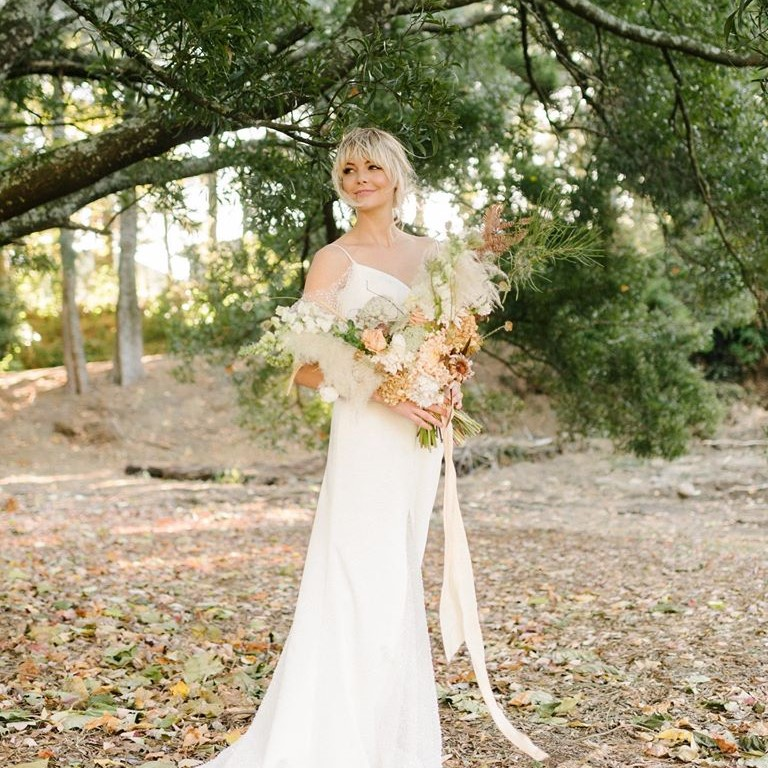 a bohemian blonde bride standing in the forest at the 'Lazy River Lodge' in her wedding dress and holding flowers